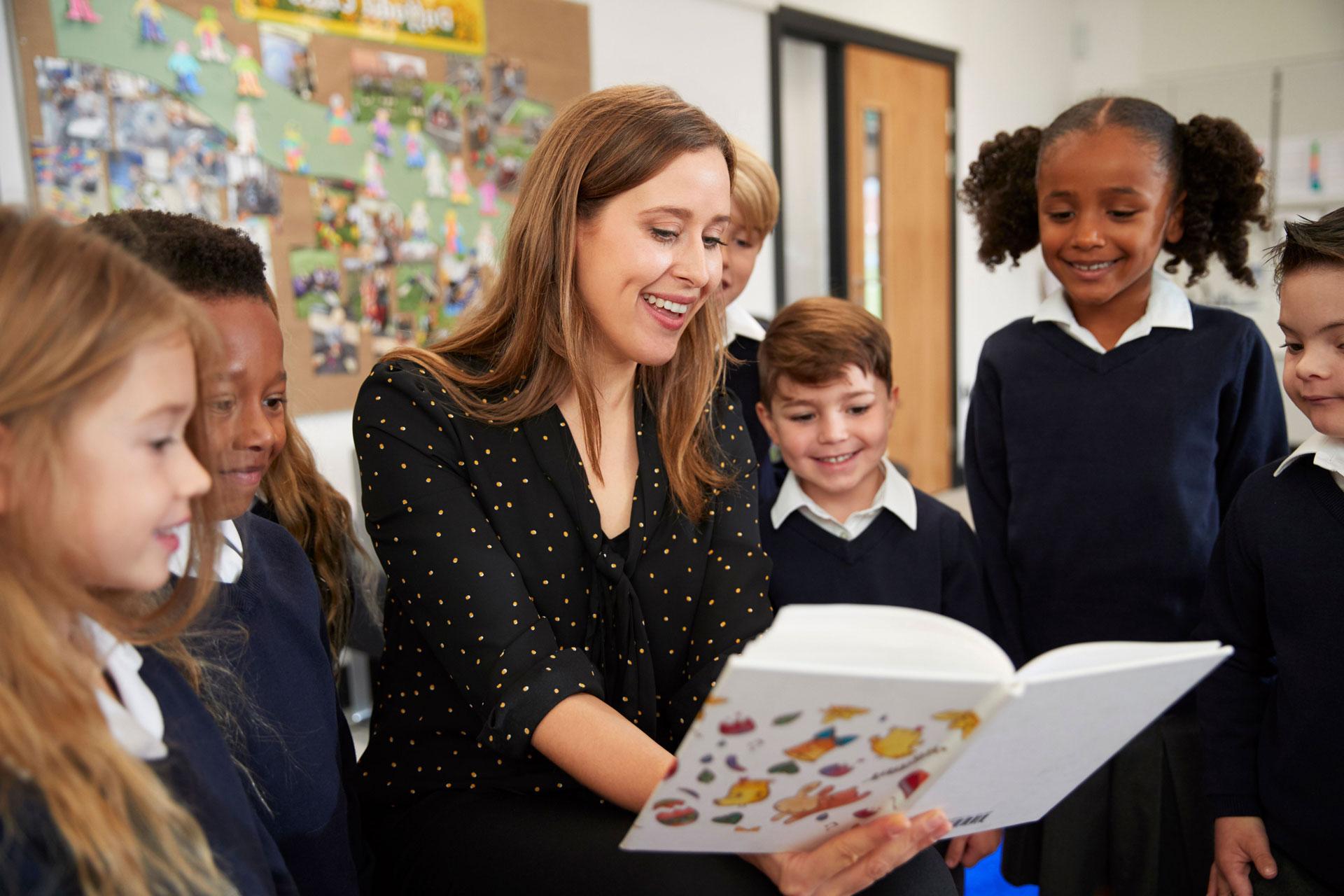 female-primary-school-teacher-reading-to-a-class-C65QJRL-rotate.jpg